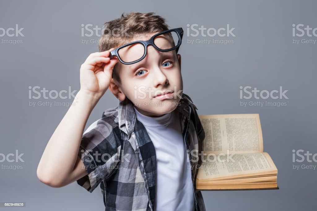 Smart pupil in glasses with textbook in hands foto de stock libre de derechos
