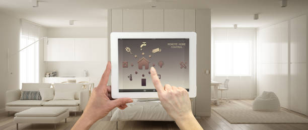 Smart remote home control system on a digital tablet. Device with app icons. One room apartment, kitchen with table, sofa and murphy bed in the background, architecture interior design stock photo