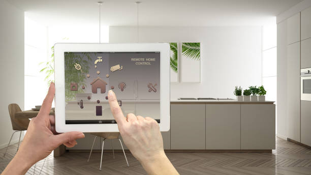 Smart remote home control system on a digital tablet. Device with app icons. Minimalist modern bright kitchen in the background, architecture interior design stock photo