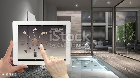 istock Smart remote home control system on a digital tablet. Device with app icons. Interior of minimalist house in the background, architecture design 943778110