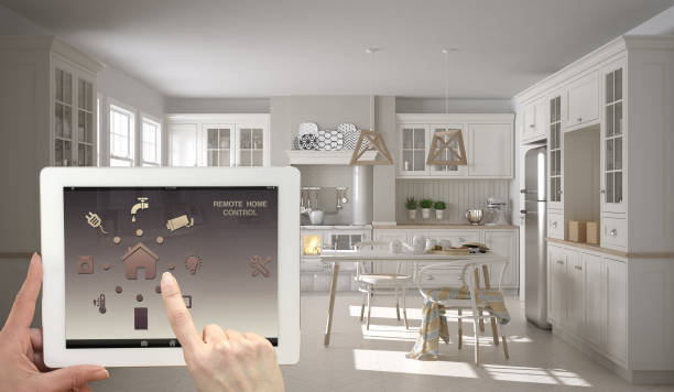 Smart remote home control system on a digital tablet. Device with app icons. Interior of scandinavian white and wooden kitchen in the background, architecture design. Smart remote home control system on a digital tablet. Device with app icons. Interior of scandinavian white and wooden kitchen in the background, architecture design. home automation stock pictures, royalty-free photos & images