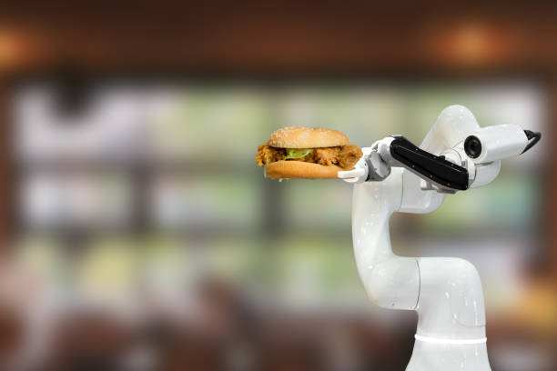Smart robotic food holding a hamburger in a restaurant futuristic robot automation increase efficiency stock photo