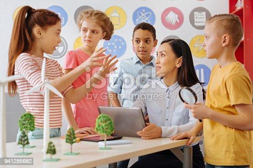 istock Smart schoolchildren sharing their ecology project idea with teacher 941285682