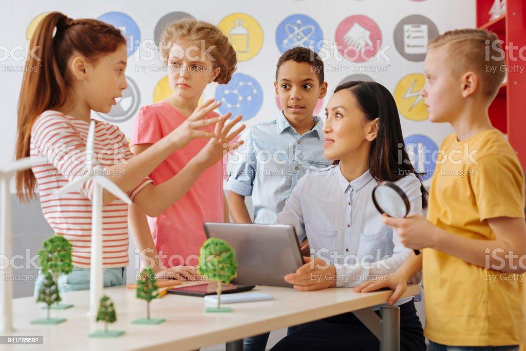Crianças em idade escolar inteligentes compartilhar sua ideia de projeto ecologia com professor - foto de acervo