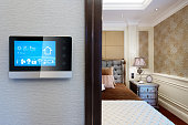 smart touching screen with smart home on wall and backgrounds of modern bedroom