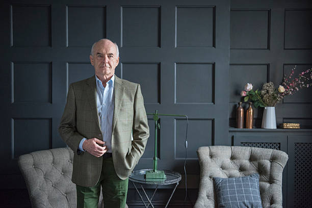 Smart senior man in grey wood panelled living room Senior man wearing jacket in sitting room looking at camera. Man with serious expression standing in modern room with armchairs and panelling on walls. high society stock pictures, royalty-free photos & images