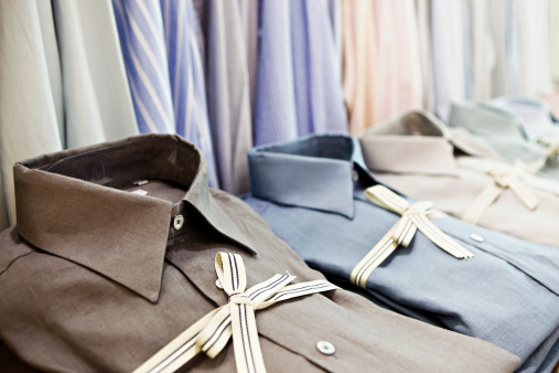 Smart shirts tied with striped ribbon in exclusive menswear store stock photo