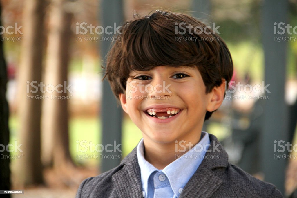Smart smily boy looking at the camera in a park stock photo