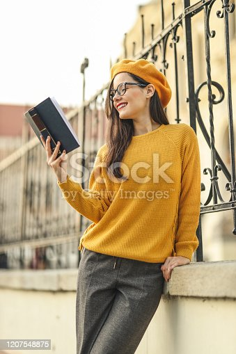 521911045 istock photo Smart student girl reading a book 1207548875