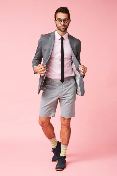 Smart suit and shorts Smart suit and shorts guy in pink studio, portrait shorts stock pictures, royalty-free photos & images