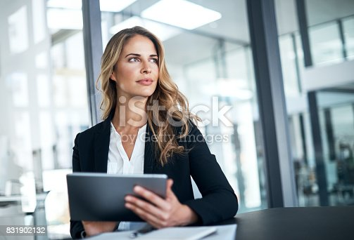 Shot of a businesswoman using a digital tablet at her desk in a modern office