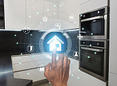 Smart technologies concept. Millennial guy using modern home control system in kitchen, collage with icons on virtual screen