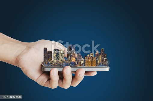 1082409706 istock photo Smart technology, smart city innovation. Hand holding mobile smart phone and building hologram 1071597496