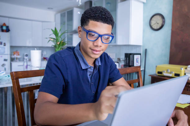 Smart teenage boy uses laptop computer to do homework in kitchen stock photo
