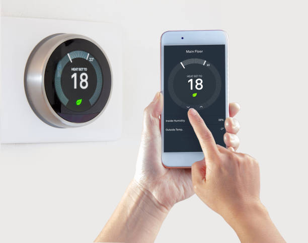 Smart Thermostat with a person saving energy with a smart device on a white background Smart Thermostat with a person saving energy with a smart device on a white background smart thermostat stock pictures, royalty-free photos & images