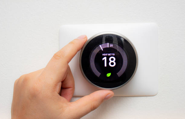 Smart Thermostat with a person saving energy with a soft shadow Smart Thermostat with a person saving energy with a soft shadow smart thermostat stock pictures, royalty-free photos & images