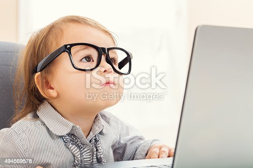 istock Smart toddler girl wearing big glasses while using her laptop 494569578