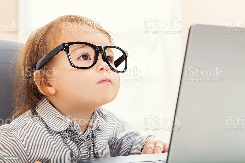 Smart toddler girl wearing big glasses while using her laptop stock photo