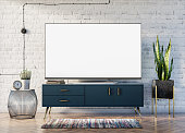 Smart TV blank screen in loft interior with a brick wall, a stylish blue cabinet with golden accents and a Sansevieria plant enlivening the space