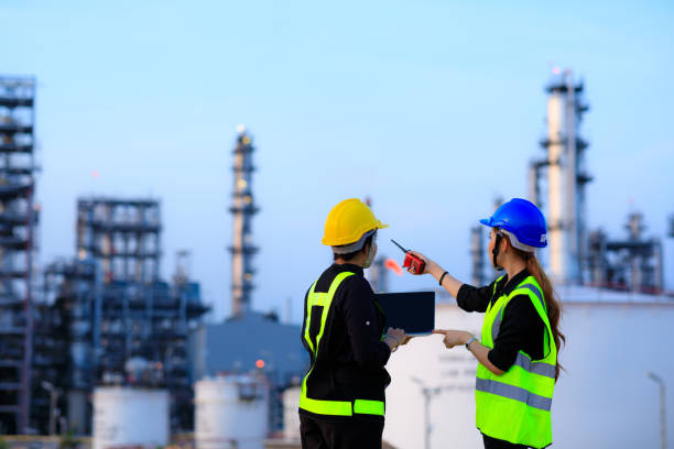 Smart two female engineer discussion together at refinery industry plant at industry factory center area. Engineering Concept Smart two female engineer discussion together at refinery industry plant at industry factory center area. Engineering Concept chemical plant stock pictures, royalty-free photos & images