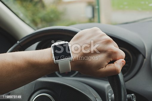 smart watch on the hand of car driver, close up