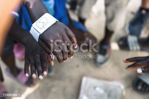 african boy showing his paper made wristwatch
