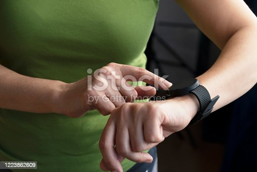 Unrecognizable caucasian woman is wearing a green t-shirt is using smart watch in front of a dark wall.