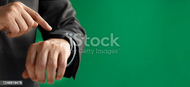Businessman is using smart watch in front of a green wall.