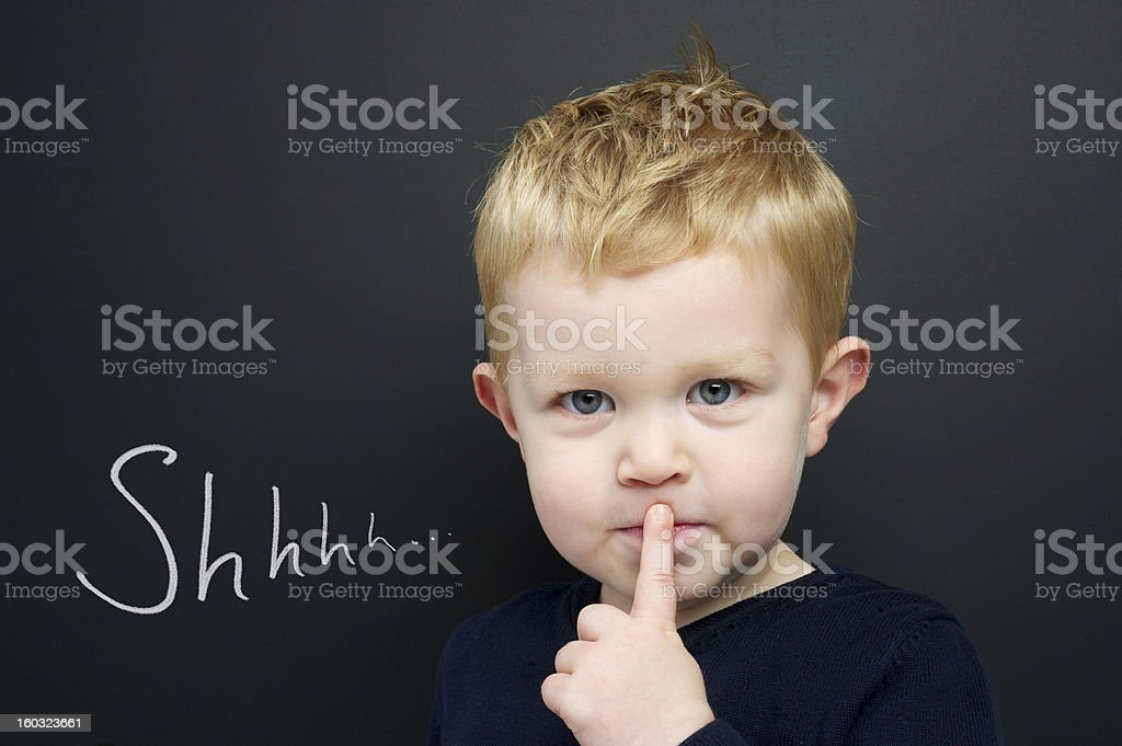 Smart young boy stood infront of a blackboard stock photo
