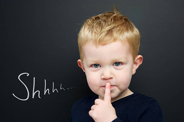 Smart young boy stood infront of a blackboard Smart young boy wearing a navy blue jumper stood infront of a blackboard with his finger over his lips being quiet finger on lips stock pictures, royalty-free photos & images