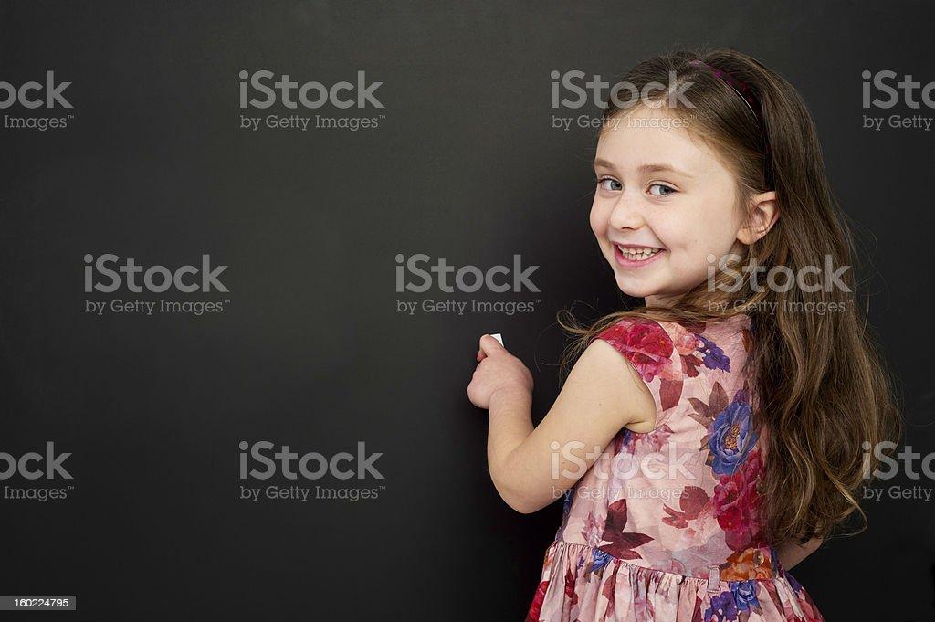 Smart young girl stood writing on a blackboard stock photo