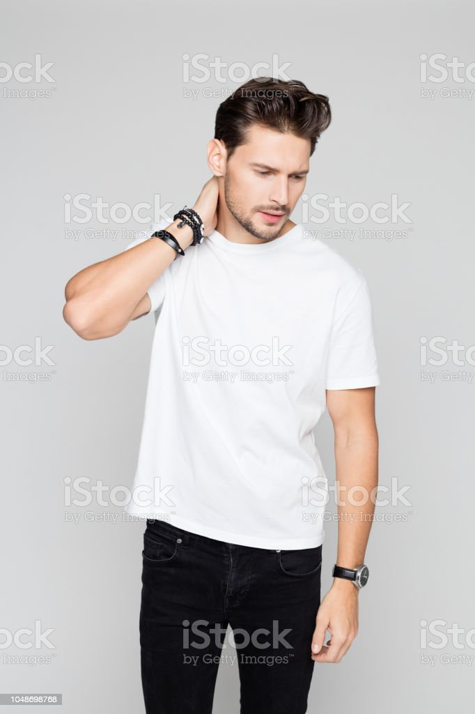 Smart young man posing on grey background Portrait of smart young man posing on grey background 25-29 Years Stock Photo