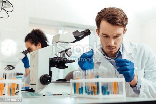 istock Smart young man working as a biologist 1156456277