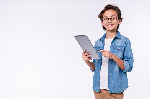 Smart young white boy using tablet in casual outfit isolated over white background