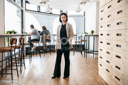 Confidence mid adult woman with hand in jacket pocket, looking at camera, corporate business, manager