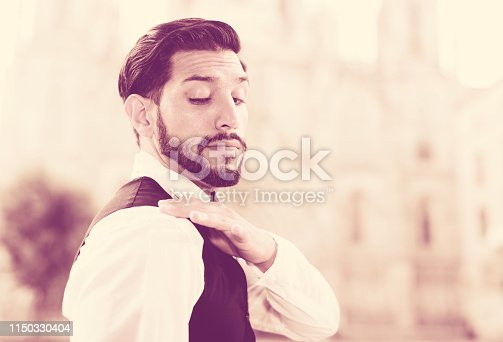 Handsome smartly dressed man standing outdoors shaking dust off shoulder
