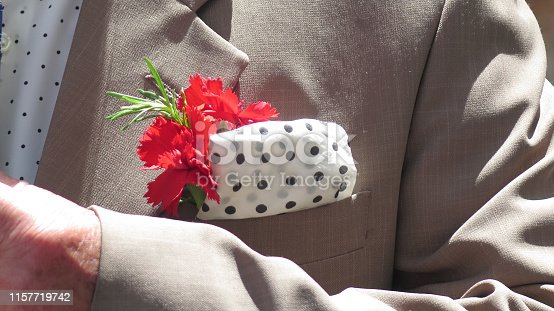 Man with polka-dot handkerchief and red carnation