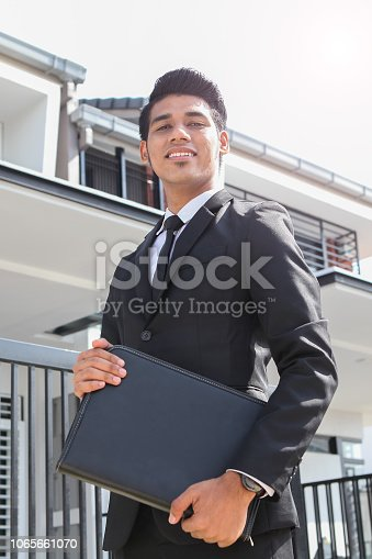 A smartly dressed and smiling real estate agent holding a black folder in front of a home property, looking confident.