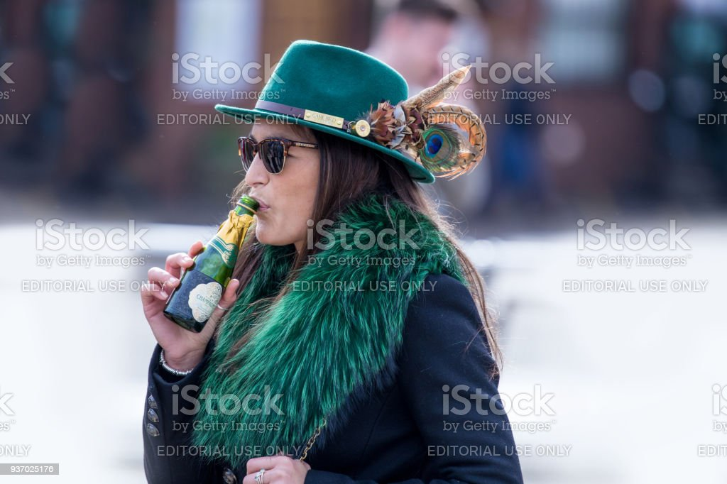 Smartly dressed woman racegoer enjoying an early tipple of champagne, mingling with the large crowds in Cheltenham on her way to the world famous Cheltenham Hunt Festival. Dressed in the green of Ireland. stock photo
