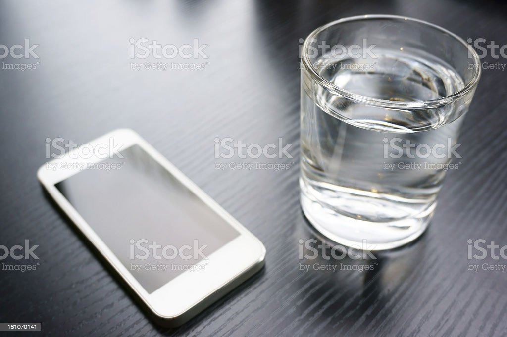 A smartphone and a glass of water on a table stock photo