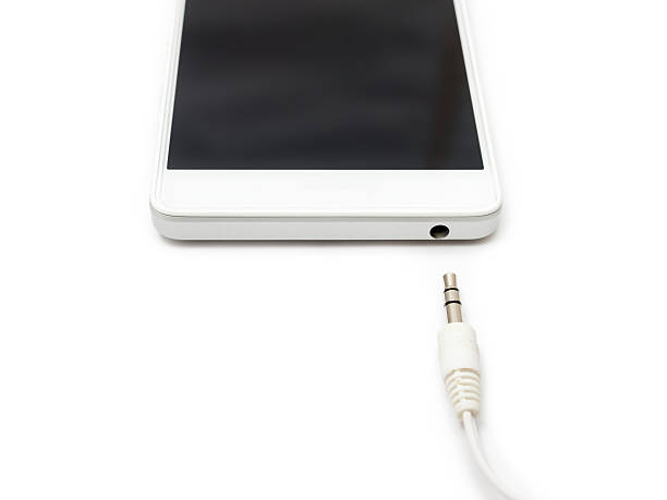 Smartphone and Audio Cable Disconnected Mini audio cable disconnected from the smartphone. White background isolated. detach stock pictures, royalty-free photos & images