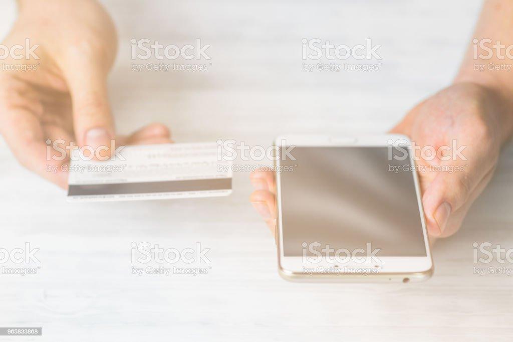 Smartphone en creditcard in de handen van een man op een witte achtergrond, concepten van internethandel en het gebruik van online bankieren te betalen voor diensten en goederen in Internet, bovenaanzicht. Lichte toning - Royalty-free Bank - Financieel gebouw Stockfoto