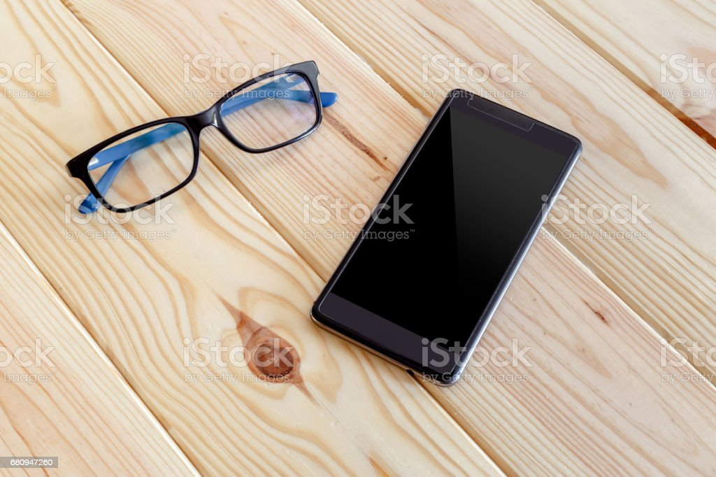Smartphone and glasses mockup on a wooden table royalty-free stock photo