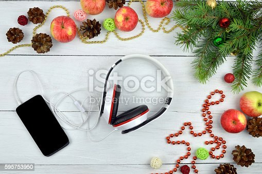 istock Smartphone and headphone  with rustic Christmas decorations. Christmas melodies. 595753950