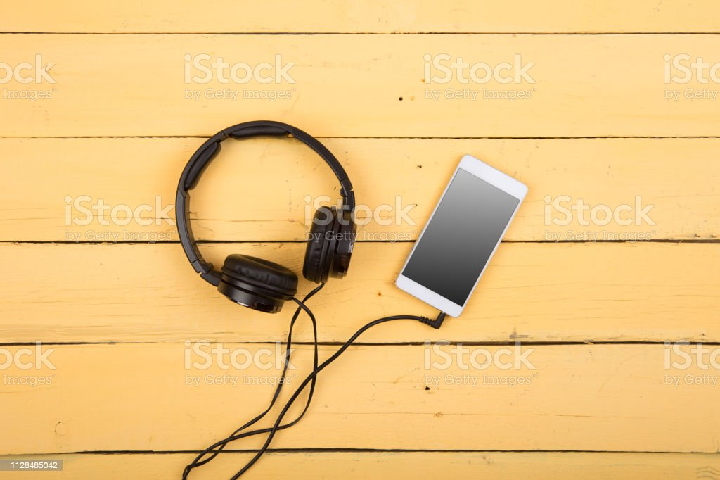 Smartphone And Headphones On The Wooden Background Listen To