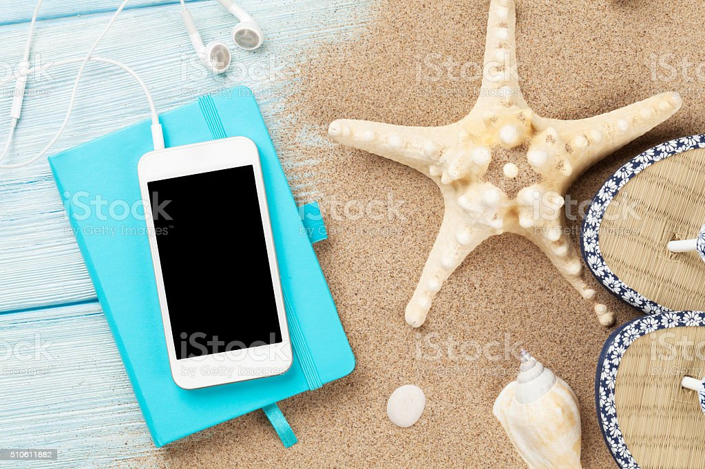 Smartphone and notepad on wood with starfish and shells stock photo