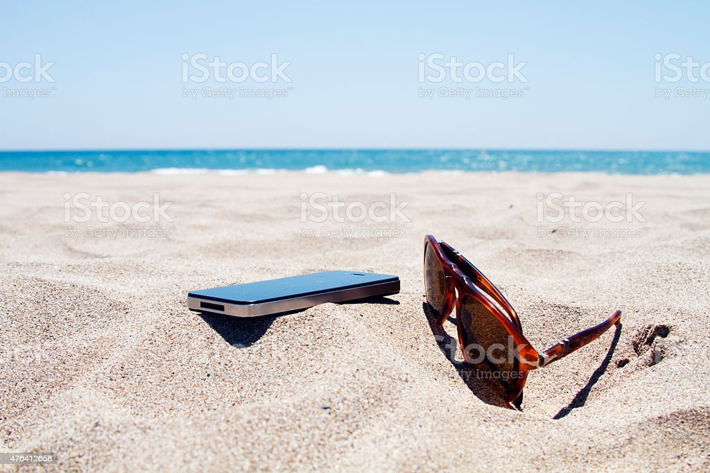 Smartphone and sunglasses on the beach stock photo