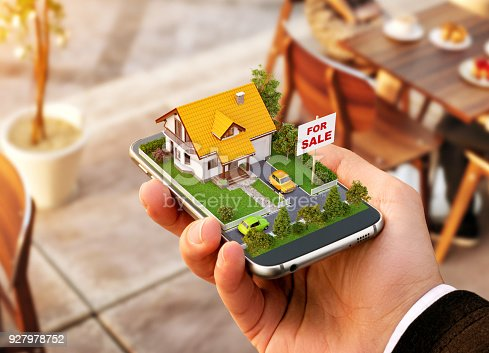 istock Smartphone application for online searching, buying, selling and booking real estate. Unusual 3D illustration of beautiful house on smart phone in hand 927978752