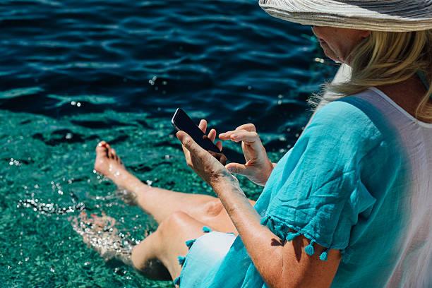 smartphone by the pool - com os pés na água - fotografias e filmes do acervo