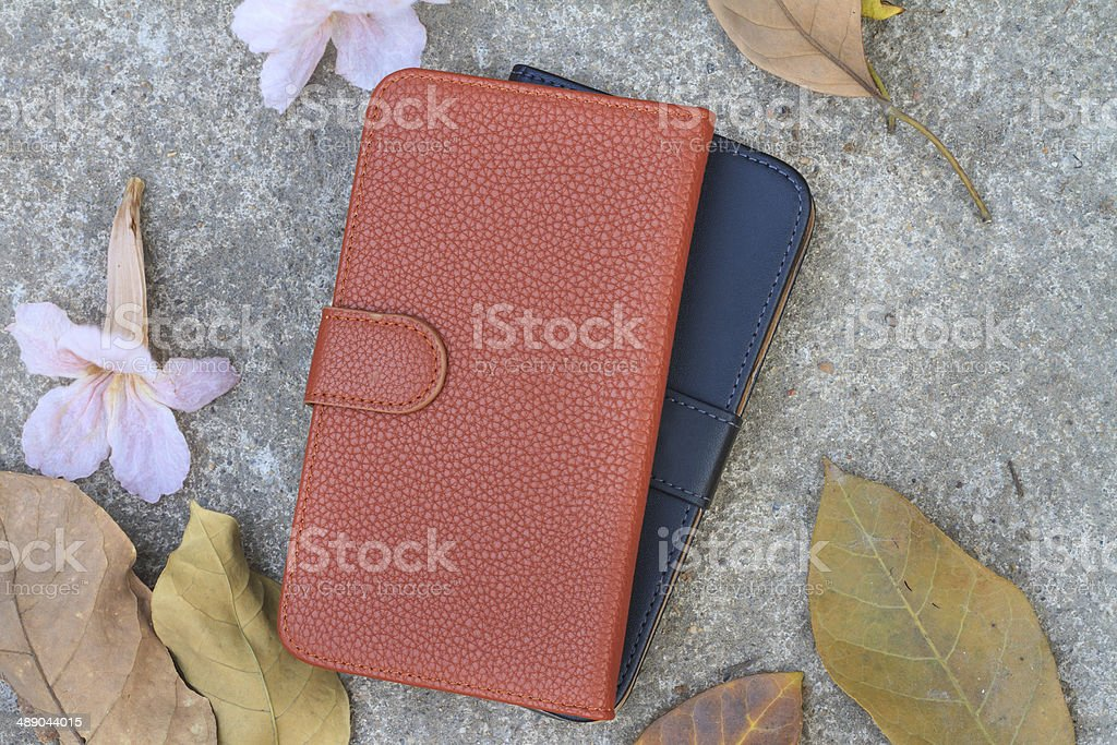 Smartphone case with dried leafs and flower on the floor royalty-free stock photo